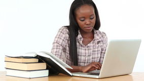 Woman typing on a laptop while reading a book. Against white background stock video