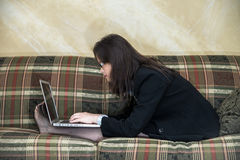 Woman typing on laptop on sofa Royalty Free Stock Image
