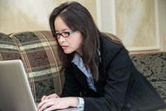 Woman typing on laptop on sofa Royalty Free Stock Photography