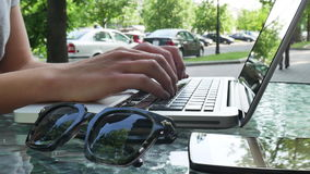 Woman typing on laptop on summer cafe stock video footage