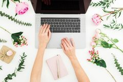 Woman typing on laptop. Workspace with female hands, laptop, notebook and pink flowers on white background. Flat lay. Woman typing on laptop. Workspace with stock photos