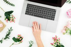 Woman typing on laptop. Workspace with female hands, laptop and pink flowers on white background. Top view. Flat lay royalty free stock images