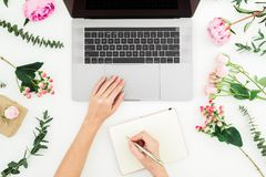 Woman typing on laptop. Workspace with female hands, laptop, notebook and pink flowers on white. Flat lay royalty free stock images