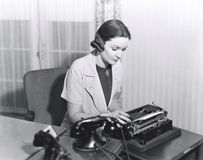 Woman typing a letter stock image