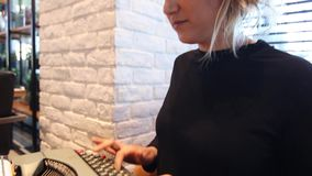 Woman with typing machine in a cafe stock video footage