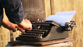 Woman Typing On Manual Vintage Typewriter At. Close-up view of a woman hands in black clothes typing on a vintage manual typewriter on white sheet of paper. The stock video footage