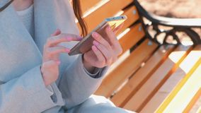 Woman typing a message in her phone sitting on the bench in park. Close-up hands. Woman typing a message in her phone sitting on the bench in park. Close-up stock video footage