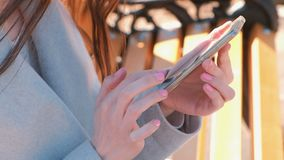 Woman typing a message in her phone sitting on the bench in park. Close-up hands. Woman typing a message in her phone sitting on the bench in park. Close-up stock video
