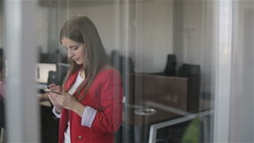 A woman typing a message on her phone. A young girl with brown hair in a red jacket standing in an office and writing messages on the phone stock footage