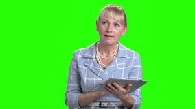 Woman typing a message on pc tablet. Elegant mature female using digital tablet on green screen background stock video footage