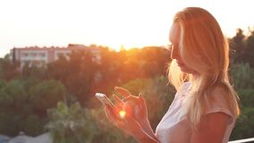 Woman typing message on smartphone on the sunset. Slow motion. Woman typing message on smartphone on the sunset. Slow motion stock footage