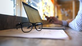Woman typing message on smartphone. Close up, glasses in the foreground stock video