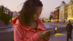 Woman typing in mobile phone against evening city. Woman typing in mobile phone on the background of the evening city stock video