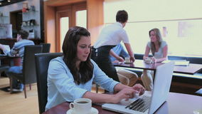 Woman typing on the notebook in canteen Stock Photos