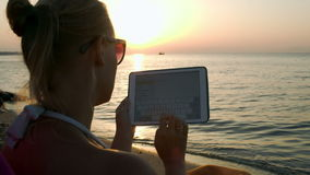 Woman typing on pad sitting by sea at sunset. Woman typing on tablet computer sitting on beach at sunset. Vacation with pad stock footage
