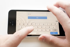 Woman typing the password for gmail account login on iphone 5c. stock photo