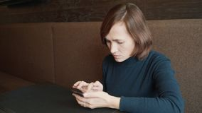 Woman typing text message on smart phone in a cafe. The brunette at the table in the cafe sits by phone. Woman typing text message on smart phone in a cafe. The stock footage