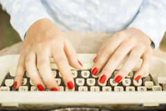 Woman typing on a typewriter Stock Images