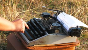 Woman Typing On Vintage Typewriter At Nature. Close-up side view of a woman hands in black clothes typing with one finder on a white sheet of paper on a vintage stock video