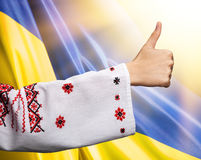 Woman in Ukrainian clothes shows symbol ok against Ukrainian fla Royalty Free Stock Image
