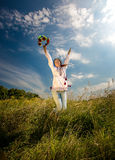 Woman in ukrainian national clothes jumping high at field Stock Images