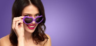 Woman with ultra violet heart shaped shades. Valentines day, beauty and people concept - close up of happy smiling young woman with lipstick and ultra violet Royalty Free Stock Photos