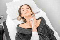 Woman during the ultrasound examination. Young woman patient during the ultrasound examination of a thyroid lying on the couch in medical office royalty free stock photo