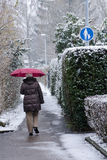 Woman with umbrealla on a sidwalk in winter Royalty Free Stock Image