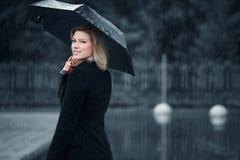 Fashion woman with umbrella walking in the rain stock photo