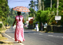 Woman with umbrella. Woman in traditional dress walking on the road, Sri Lanka Royalty Free Stock Images