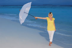 Woman with umbrella. Young woman in yellow dress standing on the beach with white umbrella in the twilight Stock Images
