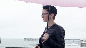 Woman under an umbrella. A woman with an umbrella admires the sea, a strong wind blows stock video footage