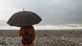 Woman with umbrella near stormy sea stock video footage