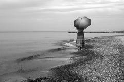 Woman with umbrella on beach Stock Photo