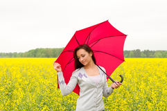 Woman with umbrella in canola field Stock Images