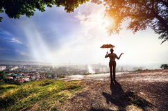 Woman with umbrella and cityscape at sunset Stock Photos
