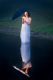 Woman with umbrella in a cold lake Royalty Free Stock Photos