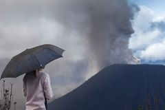 Woman with umbrella. Covered with ash watches volcano eruption. Indonesia royalty free stock photos
