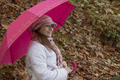 Woman with umbrella in the dry leaves Royalty Free Stock Images