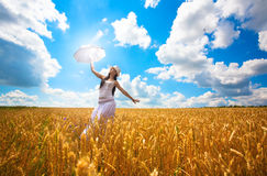 Woman with umbrella is enjoys summer day. In the field Royalty Free Stock Images