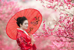 Woman with umbrella on a flowering tree branches background Stock Image