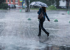 Woman with umbrella going on street during heavy rain . Woman with umbrella going on street during heavy rain rain Stock Photo