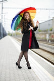 Woman with umbrella at hand welcomes observers. Woman with rainbow umbrella at hand welcomes observers Royalty Free Stock Photos