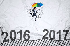Woman with umbrella jumps toward 2017 Stock Photos