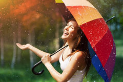 Woman with umbrella. Laughing woman with umbrella checking for rain Stock Photos