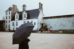 woman with umbrella looking the castle of Nantes in rainy day - France. - Nantes, FRANCE - NOVEMBER 2018 royalty free stock image
