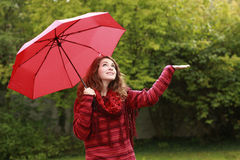 Woman with umbrella looking for rain Stock Image