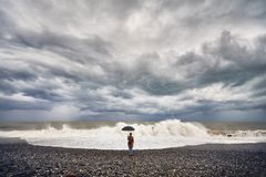 Woman with umbrella near stormy sea Stock Photos