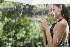 Woman with umbrella in the rain. Beautiful Hispanic woman holding umbrella out in the rain Stock Photography