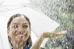 Woman with umbrella in the rain. Beautiful Hispanic woman holding umbrella out in the rain Stock Image